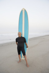 Senior surfer holding his board at the beach