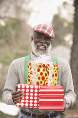 Senior African man holding presents