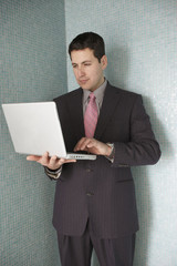 Hispanic businessman standing in a corner using his laptop