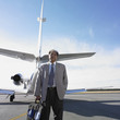 Indian businessman standing next to airplane