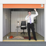 Businessman getting ready to sleep in storage unit office