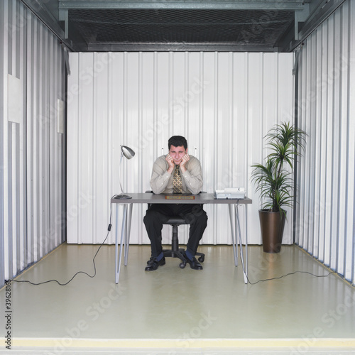Businessman sitting at desk in storage unit