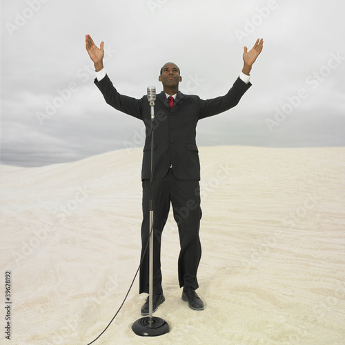 African businessman with microphone in desert