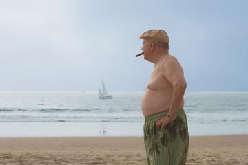 Senior man smoking a cigar on the beach