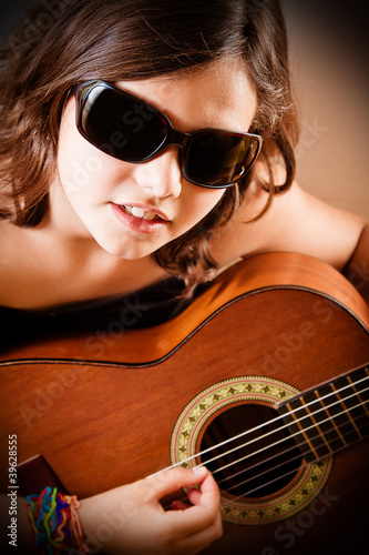Young girl playing guitar, portrait