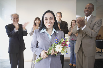 Businesswoman holding flowers while co-workers applaud