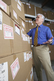 Businessman in warehouse looking at returned packages