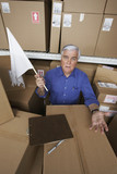 Businessman in warehouse waving white flag