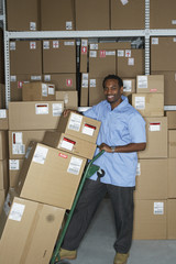 Male African warehouse worker using hand truck