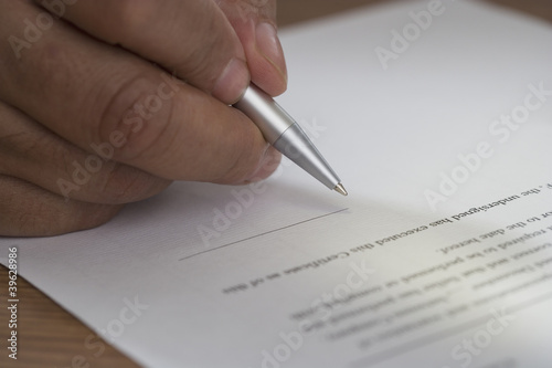 Close up of man signing document