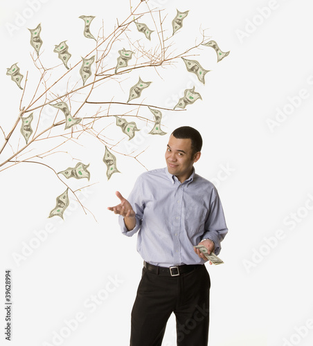 Studio shot of man with money growing on tree