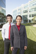 Hispanic businesswoman and businessman in front of office buildings