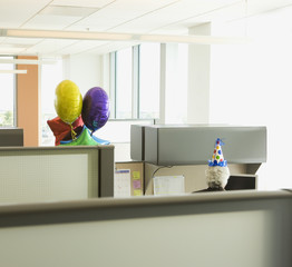 Senior woman in office with party balloons