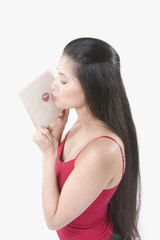 Young Asian woman making a lipstick imprint on an envelope