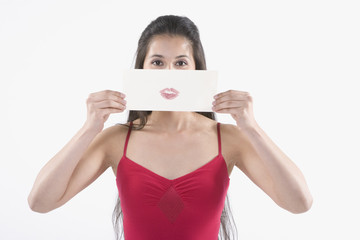 Young Hispanic woman holding a piece of paper with a lipstick imprint in front of her face