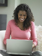 African woman using laptop on sofa