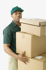 Studio shot of African delivery man with boxes