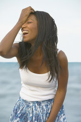 Young African woman laughing at the beach