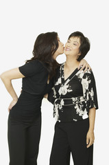 Studio shot of adult Asian daughter kissing mother on cheek