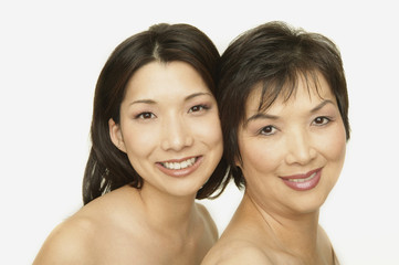 Studio shot of Asian mother and adult daughter smiling