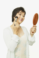 Studio shot of middle-aged Asian woman putting on make up