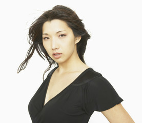 Studio shot of young Asian woman with hair blowing