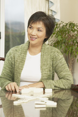 Middle-aged Asian woman playing dominoes