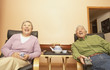 Senior Asian couple having tea while watching television