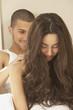 Hispanic man giving Hispanic woman a shoulder massage