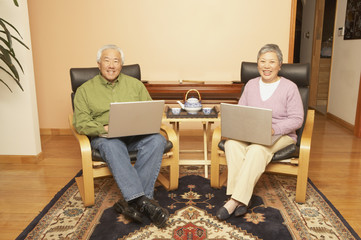 Senior Asian couple having tea while using laptops