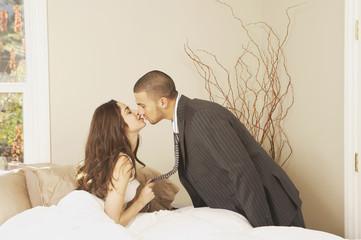 Hispanic man wearing a suit kissing Hispanic woman sitting in bed