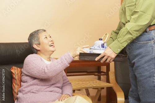 Senior Asian woman being served tea