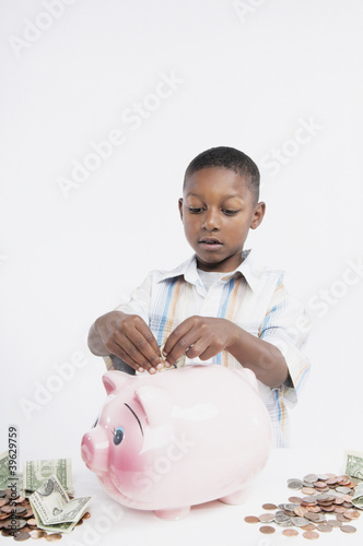 Young African boy putting money in a piggy bank