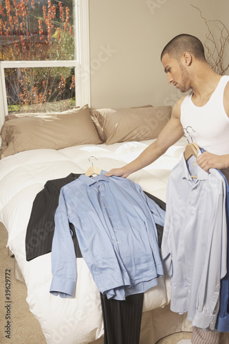 Hispanic man picking out a shirt in the bedroom