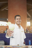 Hispanic male bartender offering up a pina colada