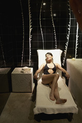 Woman in bathing suit sitting in lounge chair in spa room