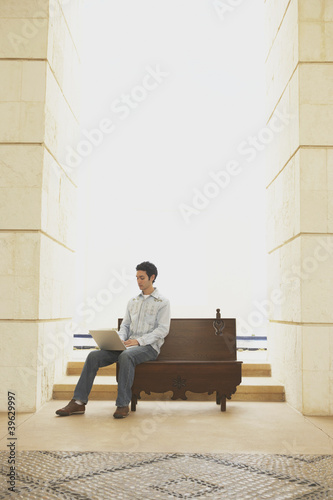Man using laptop on a bench in an open doorway