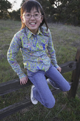 Young Asian girl sitting on a fence