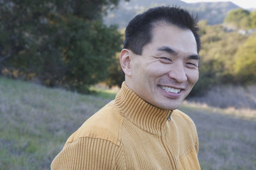 Asian man smiling in the countryside
