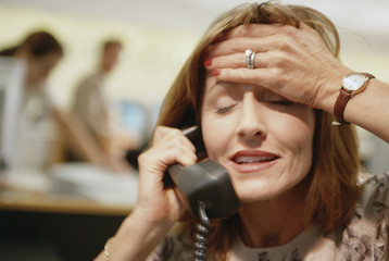 Businesswoman on telephone with her hand on her head