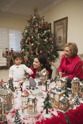 Hispanic mother and daughter playing with Christmas village