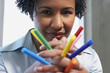 African American woman holding multicolored markers in hands