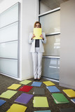 Businesswoman backed into corner by file folders