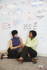 Two businesswomen sitting on floor in front of whiteboard wall
