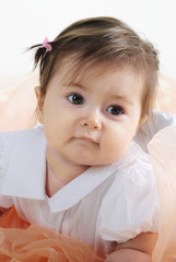 The small beautiful girl lies on a white background