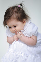 The small beautiful girl lies on a white background with toys
