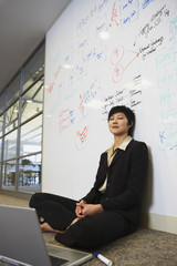 Asian businesswoman with laptop on floor in front of whiteboard wall