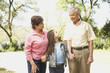 Hispanic grandparents and granddaughter holding hands outdoors