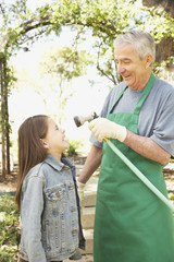 Hispanic grandfather and granddaughter playing with hose