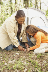 African American mother and daughter setting up tent